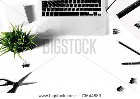 White office desk frame with laptop keyboard and supplies. Laptop, notebook, pen, clips, pencil, plant, scissors, and office supplies on white background. Flat lay, top view, mockup