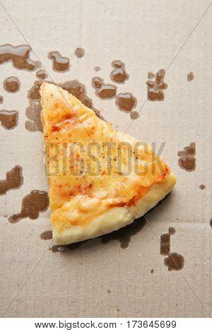 Tasty pizza slice with fat spots on cardboard