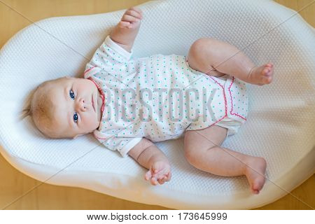 Cute adorable newborn baby againgst white background. New born child, little girl looking surprised at the camera. Family, new life, childhood, beginning concept.