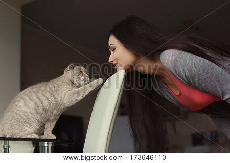 Young beautiful woman playing with cute cat at home