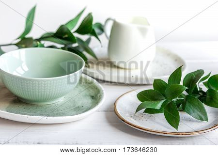 ceramic tableware with flowers on white background close up