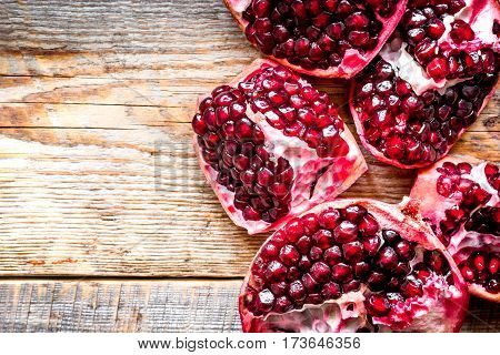 sliced pomegranate on wooden background top view.