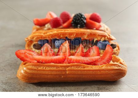 Delicious eclairs with berries on light textured background