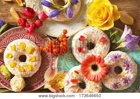 Composition of plates with delicious donuts and colourful flowers on wooden table