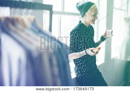 Fashion designer tattooed girl having a break with pizza