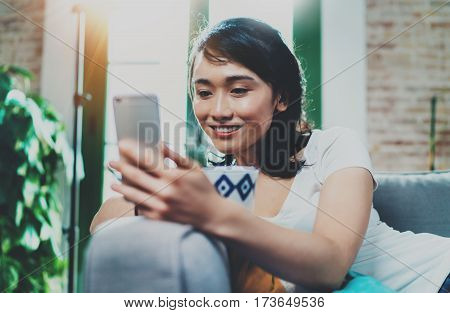 Young smiling Asian woman spending rest time at home, holding ceramic cup at hand and using smartphone for video conversation with friends.Blurred background, flares effect