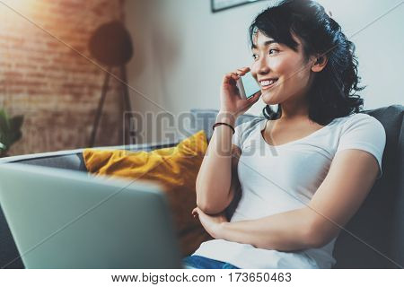 Young smiling Asian woman spending rest time at home on sofa and using smartphone for talking with friends.Blurred background, flares effect