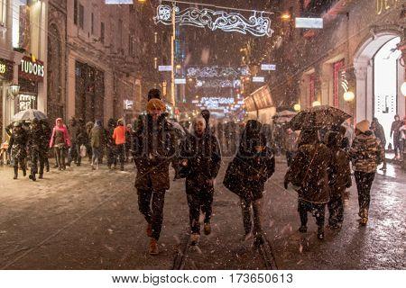 ISTANBUL TURKEY - DECEMBER 30 2015: People walking under a snowstorm on Istiklal street main pedestrian street of Istanbul Turkey