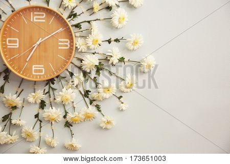 Clock decorated with flowers on wall, closeup