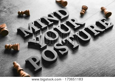 Black letters forming phrase MIND YOUR POSTURE on gray background