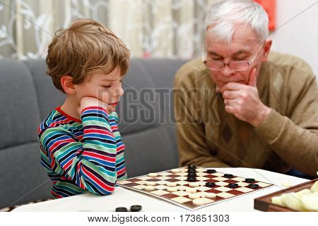 Cute little kid boy and senior grandfather playing together checkers game. Grandchild and man spending leisure together. Family having funindoors. Education skills concept