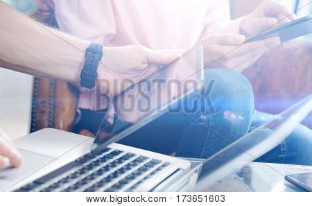Closeup view of male hand holding digital tablet.Young business team working with new startup project.Blurred background, visual effect. Horizontal.