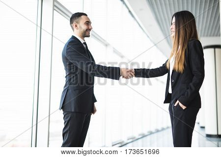 Businessman and Businesswoman handshake in office with big panoramic windows