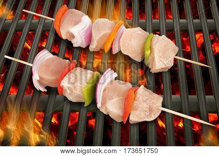 Top view of white meat skewers being grilled in a barbecue.