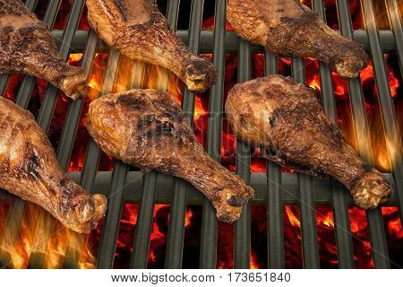 Top view of chicken drumsticks being grilled in a barbecue.