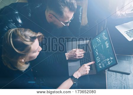 Coworking process in office.Two young colleagues using computer.Woman wearing black pullover and sitting on the sofa.Graphs, online interfaces and diagramm on laptop screen.Horizontal, visual effects