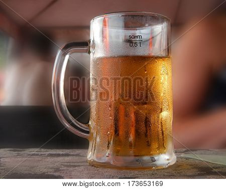 Cold beer mug with handle on table