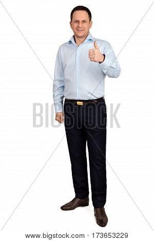Full length portrait of Young handsome man with cheerful smile in blue shirt and trousers holds his thumb up while he posing on white background