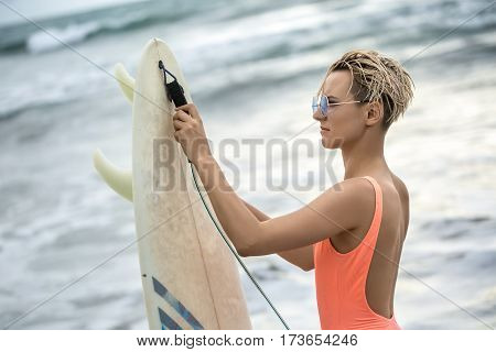 Slim blonde girl with short hairstyle stands sideways on the beach and holds the surfboard on the blurry background of the sea and the sky. She wears orange swimsuit with sunglasses. Closeup.