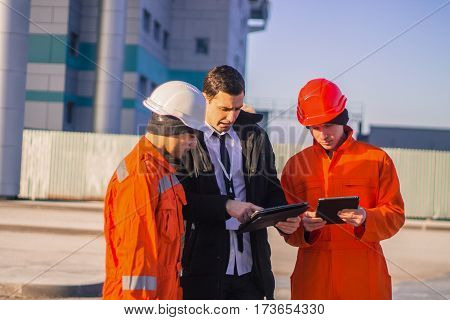 boss or Chief instructs young team of young engineers with a construction project. Business modern background