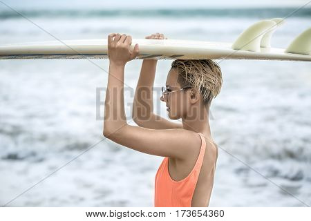 Active blonde girl with short hairstyle stands sideways on the beach on the background of the sea. She wears orange swimsuit with sunglasses and holds the surfboard on the head. Closeup. Horizontal.