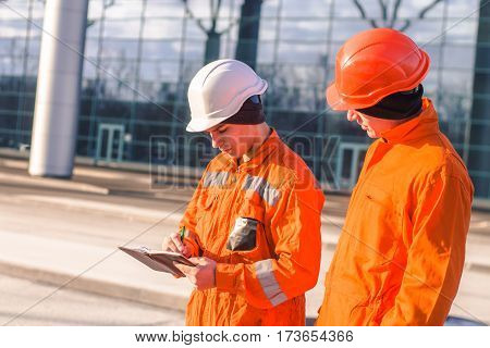 team of young engineers discussing project and writing in the note book.. The wear overalls and safety helmets. Business modern background