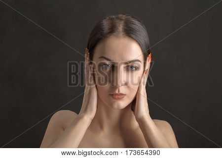 woman cover her ears on black background
