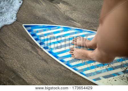 Macro photo of the female legs which are standing on the light surfboard with gray-cyan stripes on the beach. Closeup. Horizontal.