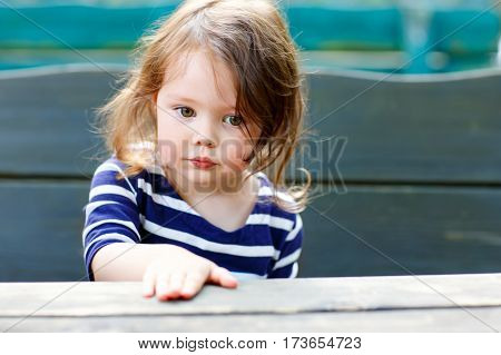 Close-up outdoor portrait of beautiful adorable toddler girl sitting by wooden table in outdoor cafe. Cute child with long hairs and in casual fashion clothes.