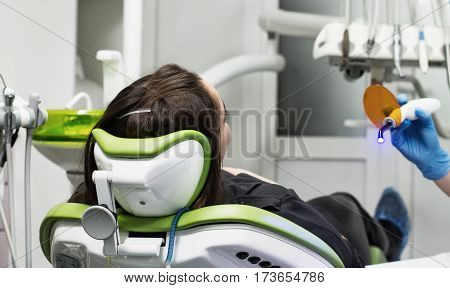 female patient at the dentist making dental fillings with ultraviolet light