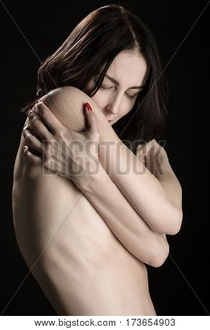 woman naked embraced herself on black background