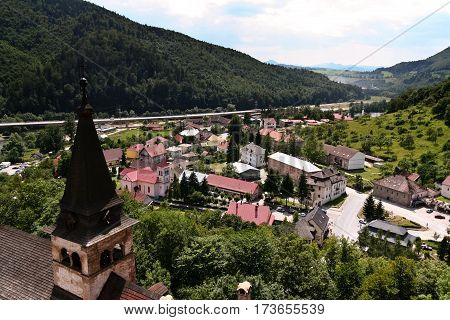 a top view of the mountains of Slovakia and a small town with houses, red and brown roofs, on the left top of the cathedral in the background mountains and skyline, cloudy, blue sky skylight,