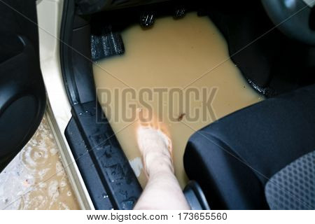 beige car got stuck in a huge pit full of dirty water on a forest road, inside the car a large pool, a naked human foot sitting down behind the wheel, man