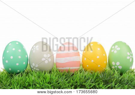 Row Of Hand Painted Easter Eggs On Grass Isolated On A White Background