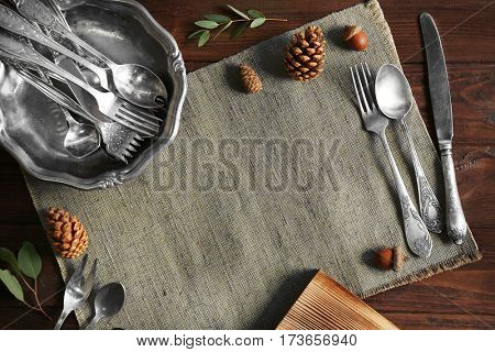 Set of silverware with napkin on wooden background
