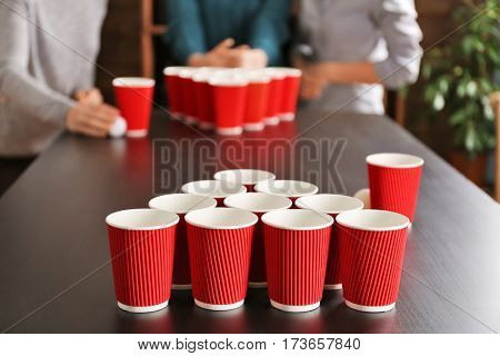 People playing Beer Pong on table at bar