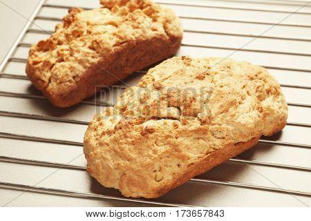 Tasty loafs of beer bread on metal grid