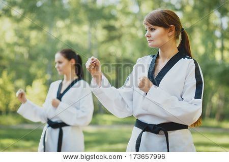 Young adult women with black belt practicing a Kata on outdoor