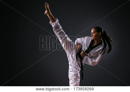 Karate girl with black belt posing on black background studio shot
