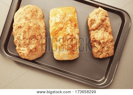 Tasty loafs of beer bread in baking tray on table