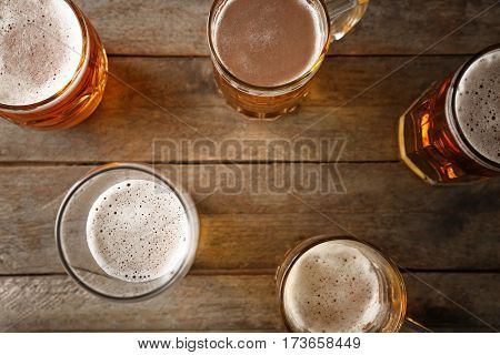Mugs with beer on wooden background