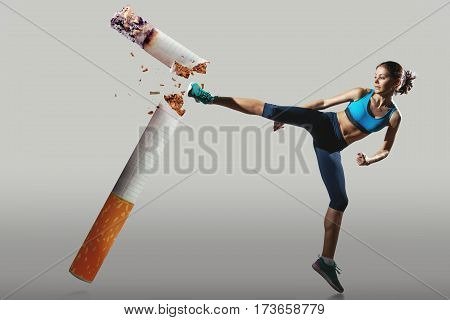 Fit young woman fighting off cigarette. Sport concept