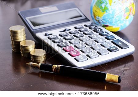 Fountain pen and calculator money coins stack and earth for Business concept