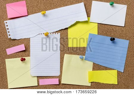 Variety of torn paper pinned to corkboard.  Lots of copy space.