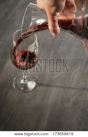 Pouring wine in glass on gray background