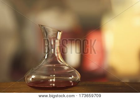 Glass carafe of red wine on blurred background
