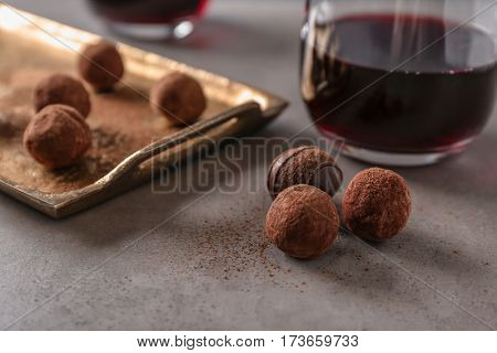 Red wine and chocolate truffles on table