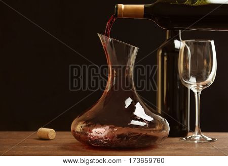 Pouring wine in carafe on wooden table