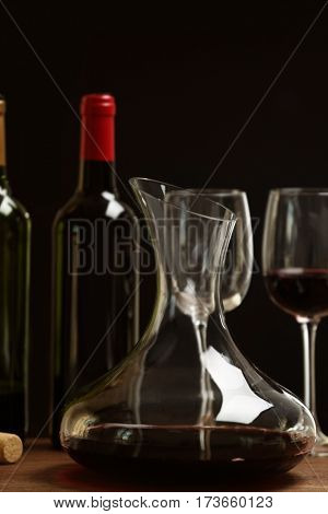 Decanter and glasses with red wine on wooden table