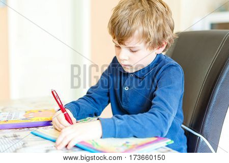 Cute little preschool kid boy at home making homework, writing letters with colorful pens. Little child doing excercise with pencils, indoors. Elementary school and education, imagine fantasy concept.
